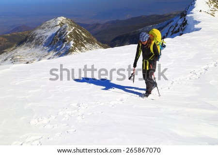 Sunny plateau covered with snow on the mountain and isolated mountaineer carrying a backpack - stock photo