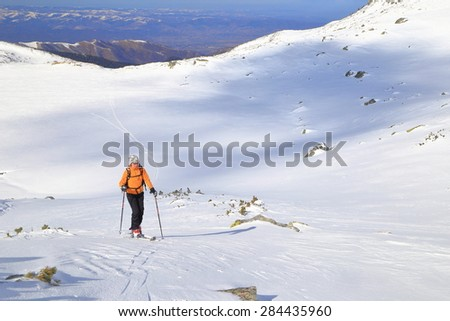 Sunny plateau on the mountain and woman on touring skis traversing an easy slope - stock photo