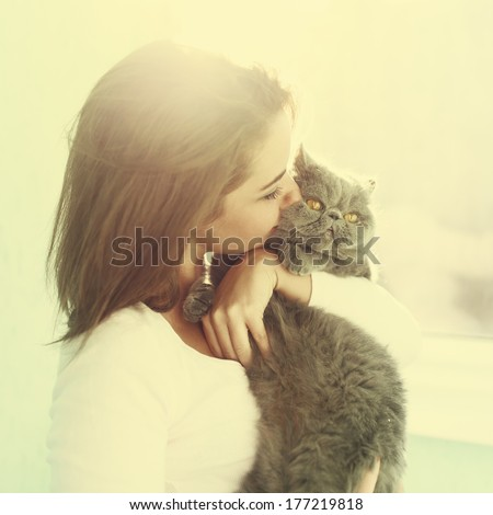 Sunny portrait of a girl who kisses a cat - stock photo