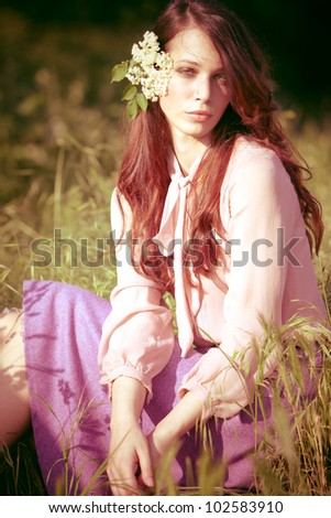 sunny portrait of a  woman sit in spring meadow with elder flower in hair - stock photo