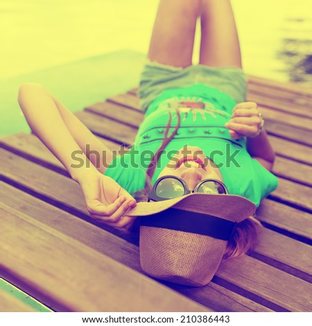 Sunny portrait of beautiful fashionable woman in sunglasses and hat lying