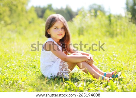 Sunny portrait of beautiful little girl sitting on the grass in summer day - stock photo