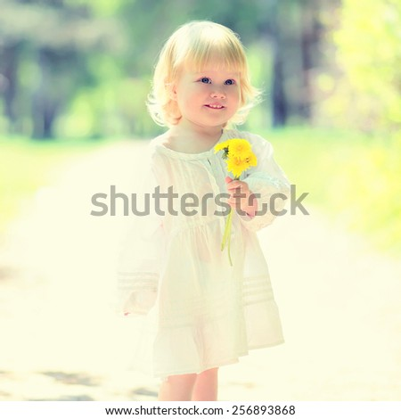 Sunny portrait of cute child with yellow dandelion in summer day - stock photo