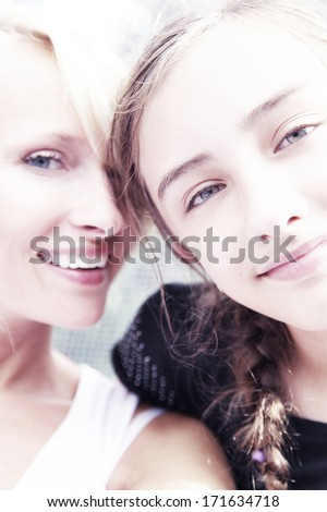 Sunny portrait of two sisters looking at camera. - stock photo