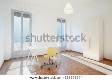 Sunny room studio with desk and chair in new apartment - stock photo