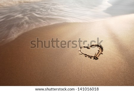 Sunny sea love sign on sand with wave. Neutral densitiy filter used to make blurry waves. - stock photo