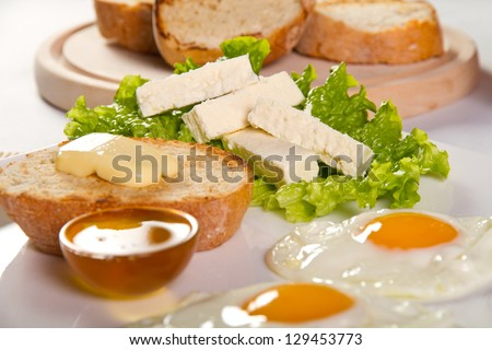 Sunny side eggs, honey and cheese breakfast (focus on cheese)