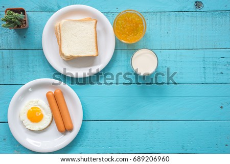 sunny side up eggs,sausage, bread, milk, orange jam