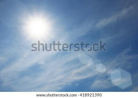 Sunny sky blue lens flare background - stock photo