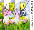 sunny spring background with fence and beautiful Tulips with letters EASTER - stock photo