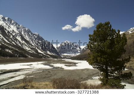 Sunny spring day, view of the snowy mountain. Beautiful landscape.