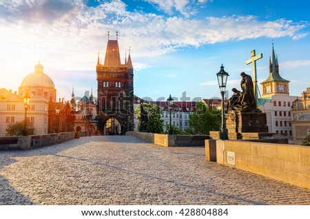 Sunny spring scene on Charles bridge on Vltava river (Karluv Most) with statues and Saint Francis of Assisi Church. Colorful morning cityscape in Prague, Czech Republic, Europe. - stock photo