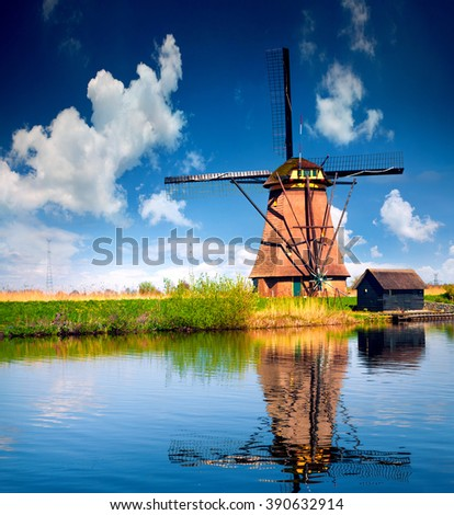 Sunny spring scene on the canal in Netherlands. Dutch windmills at Kinderdijk village, an UNESCO world heritage site. Morning in Holland, Europe. - stock photo