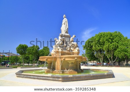 Sunny square and tall statue on top of the Pradier Fountain, Nimes, Languedoc Roussillon, France