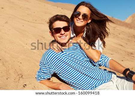 Sunny summer beautiful closeup portrait of young smiling couple in love lying in yellow sand - stock photo