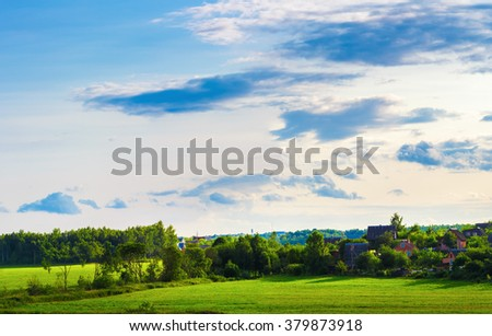 Sunny summer evening. Rural landscape. The sky with clouds, grass field, trees and farmhouses. - stock photo