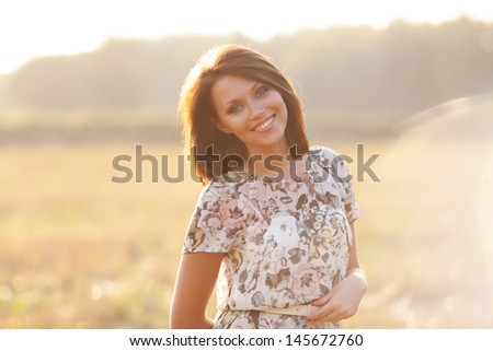 Sunny summer portrait of a beautiful smiling young woman - stock photo
