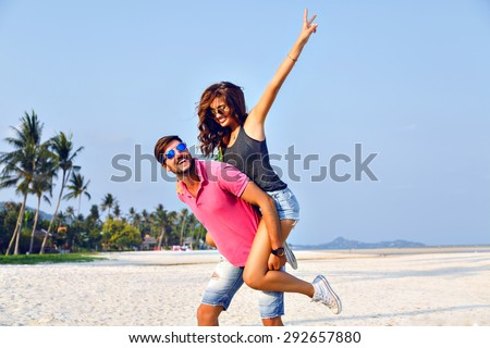 Sunny summer portrait of happy amazing beautiful couple, having fun at lonely tropical beach enjoy their vacation, trendy hipster clothes and vintage sunglasses, joy, happiness, love, relations. - stock photo