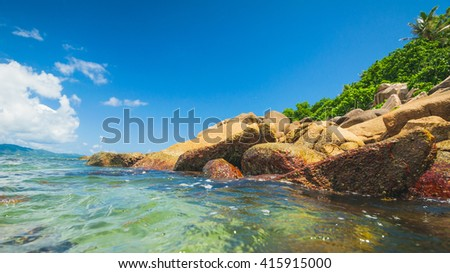 Sunny summer rocky tropical ocean shore perfect place to relax and walking in the water, Seychelles Island - stock photo