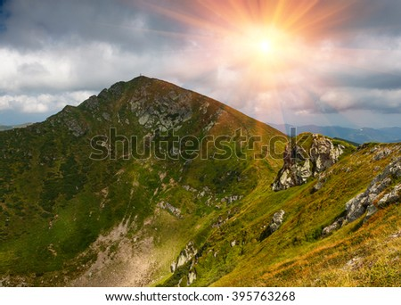 Sunny summer scene in the mountains. View of beautiful panoramic landscape of a rocky cliffs and green hills. - stock photo