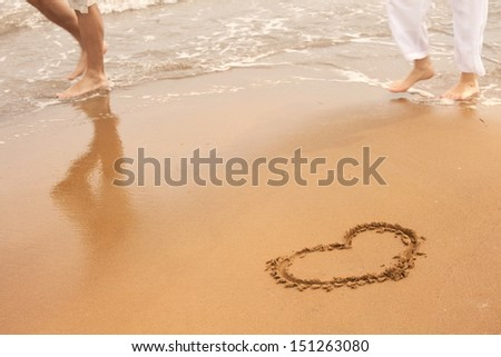 Sunny summer sea love sign on sand with wave and couple. - stock photo