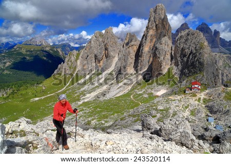Sunny trail and woman hiker in front of Torre Wundt and Savio Fonda refuge, Cadini di Misurina, Dolomite Alps, Italy - stock photo