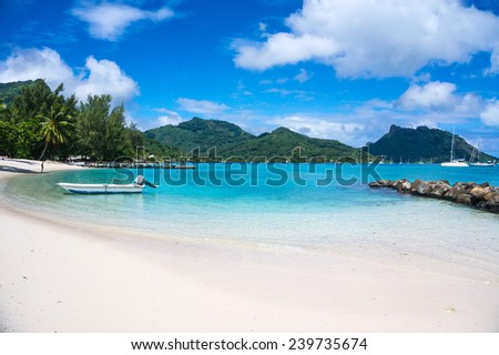 Sunny tropical beach with white sand and stone jetty, mountains in the background