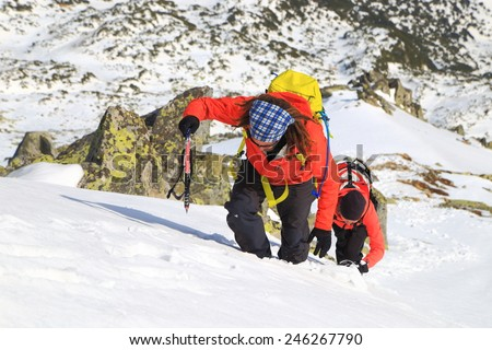 Sunny weather on the mountains and team of climbers during ascent in winter - stock photo