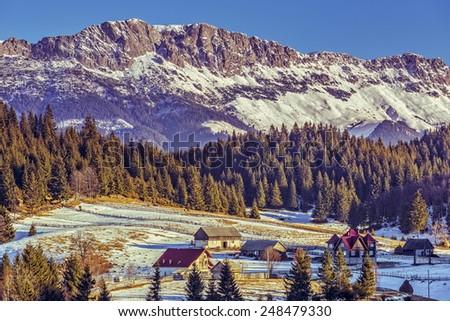 Sunny winter alpine landscape with small Romanian hamlet in the valley of Bucegi mountains range, Fundata village, Brasov county, Romania. - stock photo