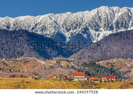 Sunny winter landscape with small remote village in the valley of snowy Piatra Craiului mountains ridge, Brasov county, Romania. - stock photo