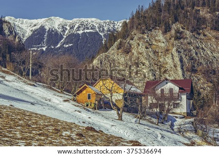 Sunny winter rural scenery with snowy Piatra Craiului mountain ridge, Romanian village and melting snow in Magura village, Brasov county, Romania.