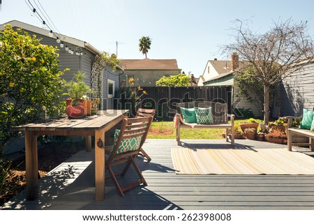 Sunny wooden outdoor deck / terrace lounge with wooden bench, decorated with pillows and blue sky. - stock photo