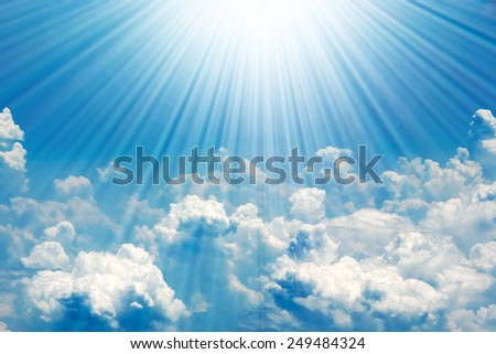Sunrays in blue sky with white clouds - stock photo