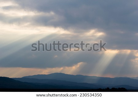Sunrays through clouds over mountain and lake, Scottish highlands - stock photo