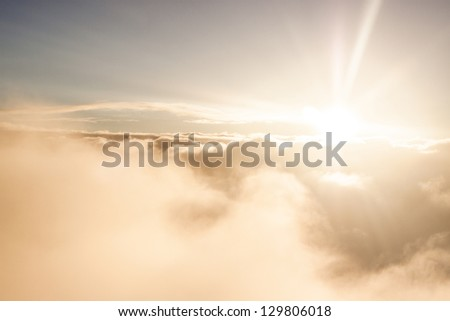 Sunrise above clouds during a flight bright light and colors - stock photo