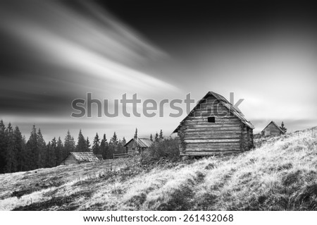 Sunrise above the nature wooden Ukrainian houses in a Carpathian mountains. Early morning, beginning of new day. Monochrome colors - stock photo