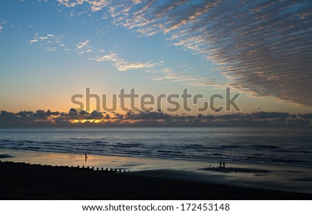 Sunrise across Hastings beach in East Sussex - stock photo