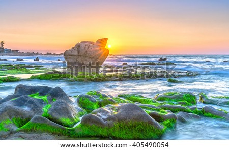 Sunrise ancient fossil reef as radiating star rounded up right edge large rock like shining pearl release, below farm yard green moss reflecting sunlight blue sky beautiful pink to welcome new day. - stock photo