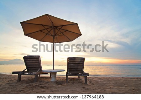 Sunrise and beach umbrella on Sanur beach, Bali - stock photo