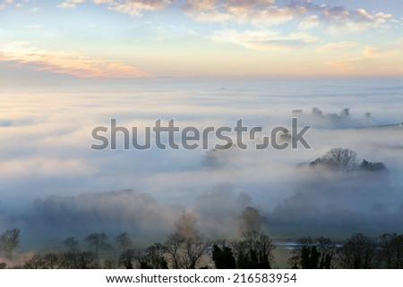 Sunrise and blue sky over fog covered landscape - stock photo