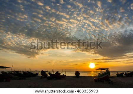 sunrise and dramatic cloud over silhouette traditional boat at the beach
