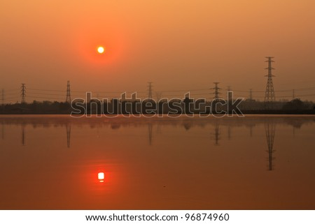 Sunrise and electric pillar with reflection in lake - stock photo