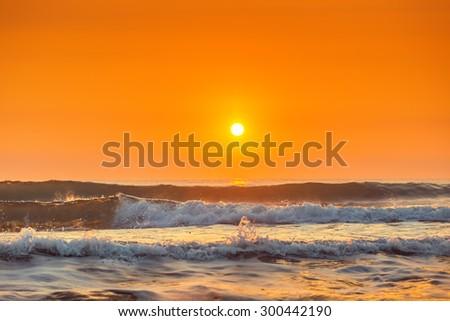 Sunrise and shining waves in ocean, sunrise shot - stock photo
