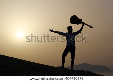 sunrise and silhouette of a happy joyful guitarist holding his guitar up in the air