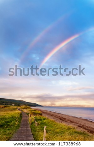 Sunrise at a beach with double rainbow early in the morning - stock photo