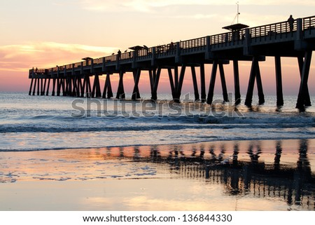 Sunrise at a fishing pier on the ocean - stock photo
