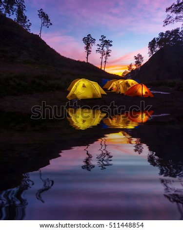 sunrise at base camp and yellow tent with water reflection