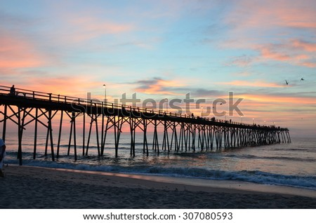 Sunrise at Kure Beach North Carolina on a warm summer morning. Seen rom near the pier.