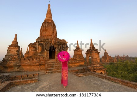Sunrise at Law Ka Ou Shaung temple with a traditionally dressed lady with umbrella in front, Bagan - Myanmar - stock photo