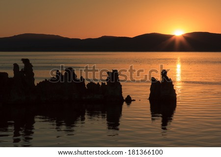 Sunrise at Mono Lake with the morning light across the tufas that rise from the waters - stock photo